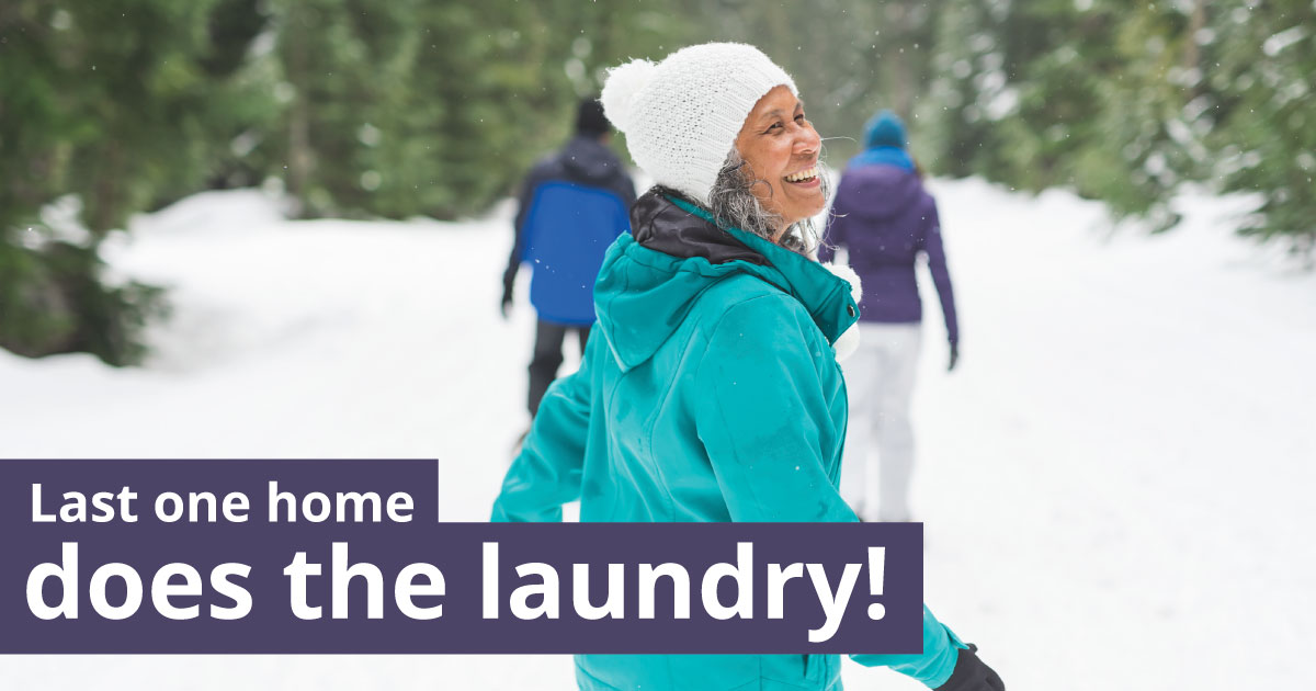 A woman walking in the snow looks behind her. Text reads: Last one home does the laundry!
